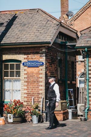 Sheringham, UK - April 21, 2019: Conductor in uniform walking on a platform of Sheringham retro train station. Sheringham is an English seaside town within the county of Norfolk, UK. Редакционное