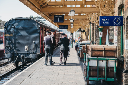 Sheringham, UK - April 21, 2019: Staff talking on platform next to The Poppy Line steam train, also known as the North Norfolk Railway, a Heritage Steam Railway that runs from Sheringham to Holt.