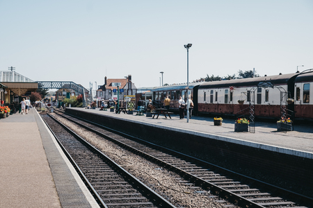 Sheringham, UK - April 21, 2019: People walking on a platform of Sheringham train station. Poppy Line train, a Heritage Steam Railway that runs from Sheringham to Holt, Norfolk, is on the background. Redactioneel