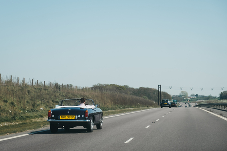 Norfolk, UK - April 21, 2019: Man driving a retro convertible car with the hood down on A11, a major trunk road in England that runs roughly north east from London to Norwich.