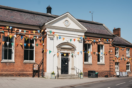 Aulsham, UK - April 21, 2019: Facade of Aysham Town Hall decorated with bunting for Easter Bank Holiday. Aylsham is a historic market town and civil parish on the River Bure in north Norfolk, England