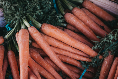 Close up of bunches of raw organic carrots in a wooden crate. Imagens