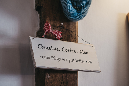 Close up of a light coloured humour sign joking about the chocolate, coffee and men. Stock Photo