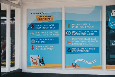 Cromer, UK - April 20, 2019: Crabbing tips and guidance poster on Cromer pier. Cromer is a seaside town in Norfolk and a popular family holiday destination in UK. Foto de archivo - 124584900
