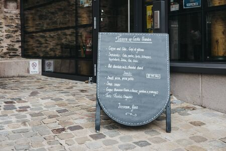 Vianden, Luxembourg - May 18, 2019: Black board menu outside of a Tavern within Vianden Castle, Luxembourg, one of the largest and finest feudal residences of the Roman and Gothic eras in Europe. 版權商用圖片 - 124585274