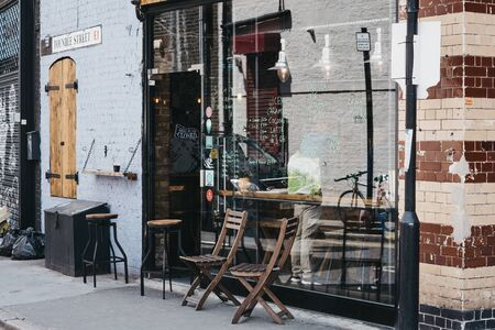 London, UK - June 22, 2019: Wooden table and chairs outside Pause cafe in Shoreditch, a trendy area of Londons East End that is home to an array of markets, bars and restaurants.