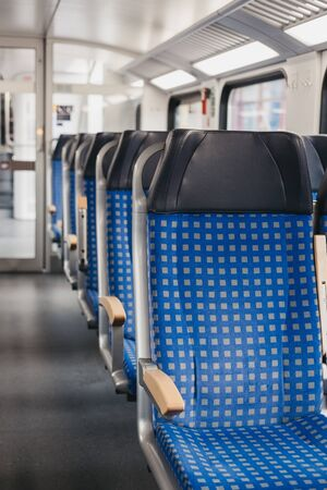 Rows of blue fabric seats with leather headrests on one side of an aisle inside empty modern train, travel concept, selective focus.