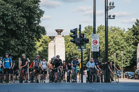 London, UK - July 15, 2019: Cyclists waiting on a red traffic light to cross a road in London, UK, in summer. Cycling is a popular way of getting around the city. Editorial