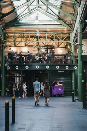 London, UK - July 23, 2019: People walking inside Borough Market, one of the largest and oldest food markets in London.