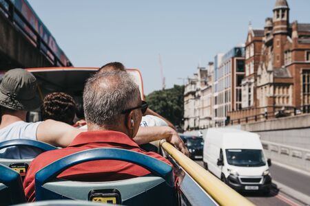 London, UK - July 29, 2019: Tourists enjoying city views from top deck of of tour bus in London on a bright summer day. Open top bus tours are amongst the most popular tourist activities in London. Redactioneel