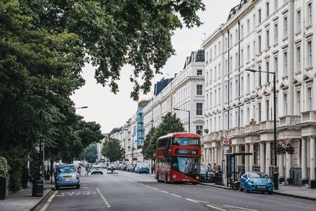 London, UK - July 16, 2019: Red double decker bus driving past a row of white terraced houses on a street in Pimlico, an upscale residential area of London with quiet streets lined with stately homes.