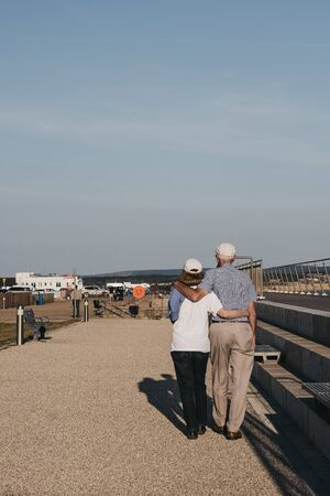 Milford on Sea, UK - July 13, 2019: Senior couple walking with arms around each other in Milford on Sea, a traditional English village famous for breathtaking cliff top walks and pebble beaches.