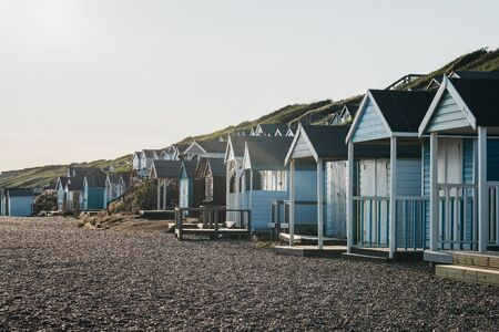 Milford on Sea, UK - July 13, 2019: Beach huts at sunset in Milford on Sea, a traditional English village famous for breathtaking cliff top walks with spectacular views and great pebble beaches