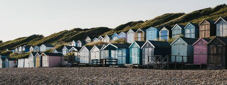 Milford on Sea,UK - July 13,2019: Panoramic view of beach huts during sunset in Milford on Sea, a traditional English village famous for cliff top walks with spectacular views and great pebble beaches