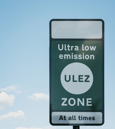 London, UK - July 15, 2019: Sign indicating Ultra Low Emission Zone (ULEZ) in London against blue sky and clouds. ULEZ was introduced in 2019 to help improve air quality in the capital.