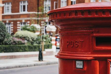 Primo piano di una casella postale rossa su una strada a Londra, Regno Unito, messa a fuoco poco profonda.