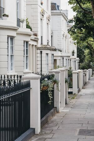 Row of white terraced houses on a street in London, UK, in summer.