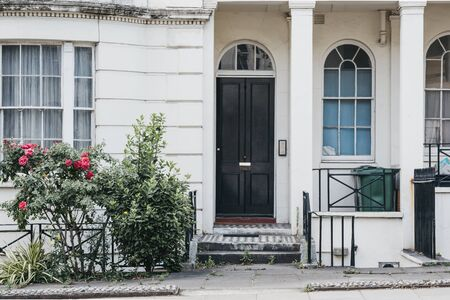White terraced house with lower ground floor and black entrance door on a street in London, UK, in summer.