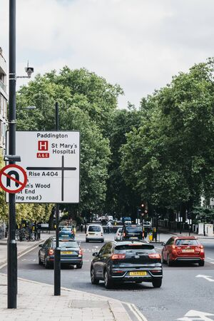 London, UK - July 18, 2019: Cars drive park directional road signs on a street in London, UK, motion blur, selective focus. London is one of the most traffic congested city in the world.