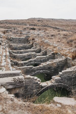 Ruins of a vast reservoir that supplied water on the island of Delos, Greece, an archaeological site near Mykonos in the Aegean Sea Cyclades archipelago.