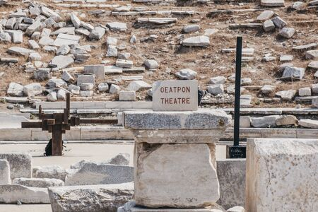 Sign at the outdoor ancient theatre on the Greek island of Delos, archaeological site near Mykonos in the Aegean Sea Cyclades archipelago. Selective focus.