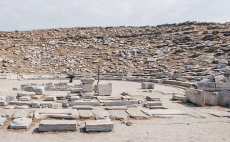Ruins of outdoor ancient theatre on the Greek island of Delos, archaeological site near Mykonos in the Aegean Sea Cyclades archipelago. Selective focus.