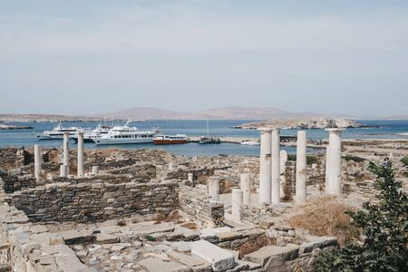 Delos, Greece - September 20, 2019: Ruins on the Island of Delos, archaeological site near Mykonos in the Aegean Sea Cyclades archipelago, tour boats docked on the background. Selective focus.