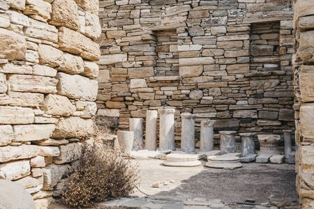 Ruins and columns in the Theatre Quarter on the island of Delos, Greece, an archaeological site near Mykonos in the Aegean Sea Cyclades archipelago.