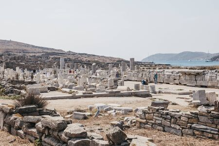 Delos, Greece - September 20, 2019: People walk by columns and ruins on the Sacred Way on the island of Delos, Greece, an archaeological site near Mykonos in the Aegean Sea Cyclades archipelago.