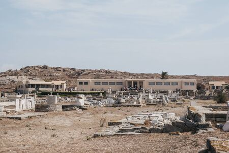 Delos, Greece - September 20. 2019: View over the ruins of people getting in the Archaeological Museum of Delos, a museum on the historic island of Delos, near Mykonos in the South Aegean, Greece.