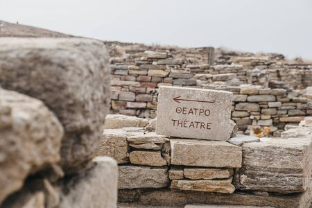 Sign toward the theatre on the Greek island of Delos, archaeological site near Mykonos in the Aegean Sea Cyclades archipelago. Selective focus.