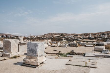 Delos, Greece - September 20, 2019: Ruins of agora on the island of Delos, Greece, an archaeological site near Mykonos in the Aegean Sea Cyclades archipelago, tour group and museum on the background.