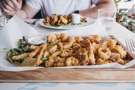 Frito misto (varied battered deep fried seafood) served on a wooden tray in a restaurant, selective focus. 스톡 콘텐츠