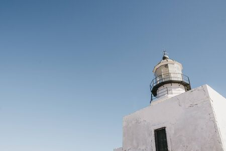 Low angle view of Armenistis Lighthouse in Mykonos, Greece, against blue sky, copy space. Stock Photo