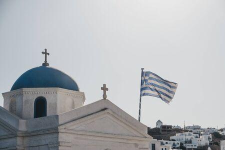 Greek flag in the wind against blur sky, on the orthodox church in Mykonos, Greece. Motion blur.