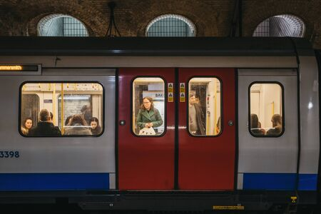 London, UK - November 26, 2019: London Underground train on a station platform, people seen though the window. London Underground is the oldest underground railway in the world. Selective focus. 에디토리얼