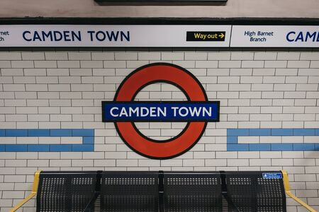 London, UK - November 26, 2019: Camden Town underground station roundel sign on the platform of Camden Town station, London. London Underground is the oldest underground railway in the world.