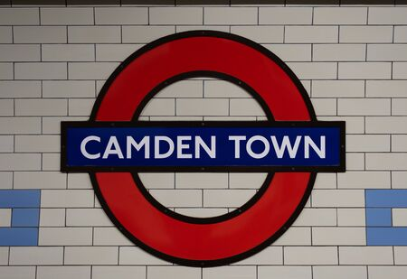 London, UK - November 26, 2019: Close up of underground station roundel sign on the platform of Camden Town station, London. London Underground is the oldest underground railway in the world.