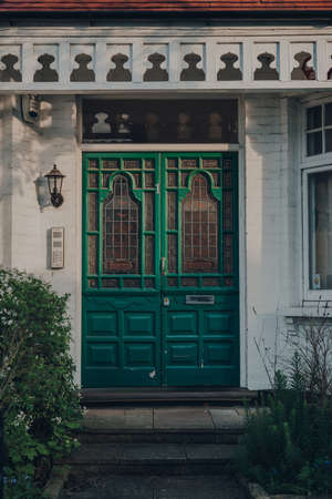 London, UK - April 12, 2020: Stained glass bright green wooden door of a traditional Edwardian house in London, UK. Edwardian houses promote simple design and an appreciation for the handmade. Editorial