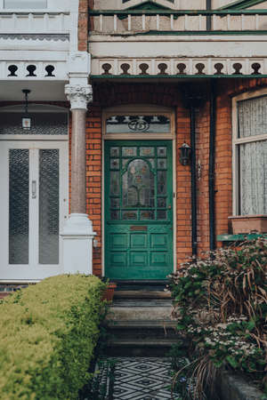 London, UK - April 12, 2020: Stained glass green wooden door of a traditional Edwardian house in London, UK. Edwardian houses promote simple design and an appreciation for the handmade.
