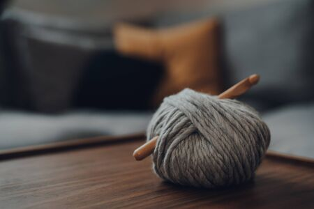 Close up of a ball of grey chunky wool yarn with a large wooden crochet hook laying on a wooden table, shallow focus, in modern Scandi interior.