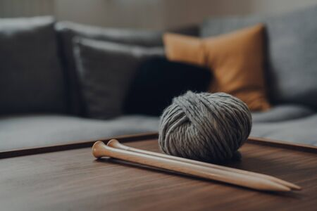 Close up of a ball of grey chunky wool yarn and a pair of large wooden knitting needles on a wooden table, shallow focus, in modern Scandi interior. Фото со стока