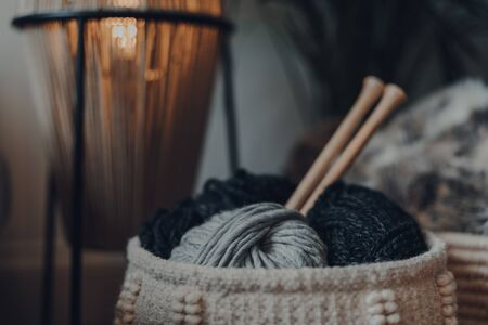 Close up of balls of yarn inside a basket, with large wooden knitting needles, shallow focus.
