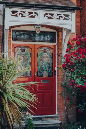 Red stained glass front door of a traditional Edwardian house in London, UK, selective focus, framed by trees and blossoming roses.