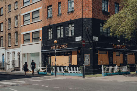 London, UK - June 13, 2020: Boarded up facade of Simmons bar in Fitzrovia, diverse area of Central London dotted with restaurants, hotels, galleries and old-school pubs, people walking past. Editöryel