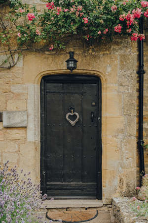 Old wooden front door of a traditional limestone house in Broadway, Cotswolds, UK.