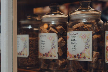 Broadway, UK - July 07, 2020: Hamiltons fudge in jars in a window of a shop in Broadway, a large historic village within the Cotswolds in the county of Worcestershire, England, selective focus.