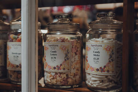 Broadway, UK - July 07, 2020: Hamiltons retro sweets in jars in a window of a shop in Broadway, a large historic village within the Cotswolds in the county of Worcestershire, England, selective focus.