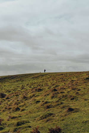 Unidentifiable man and a dog walking on the horizon line on top of a hill in Mendip Hills, UK, against the sky. 스톡 콘텐츠