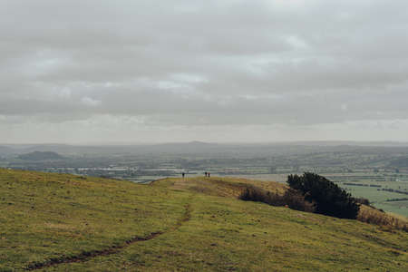 Unidentifiable people walking in the distance on top of a hill in Mendip Hills, UK, scenic view.